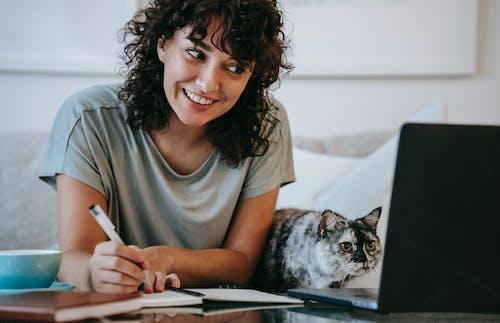 Mulher Em Uma Camiseta Cinza Com Gola Redonda Segurando Um Gato Marrom E Branco