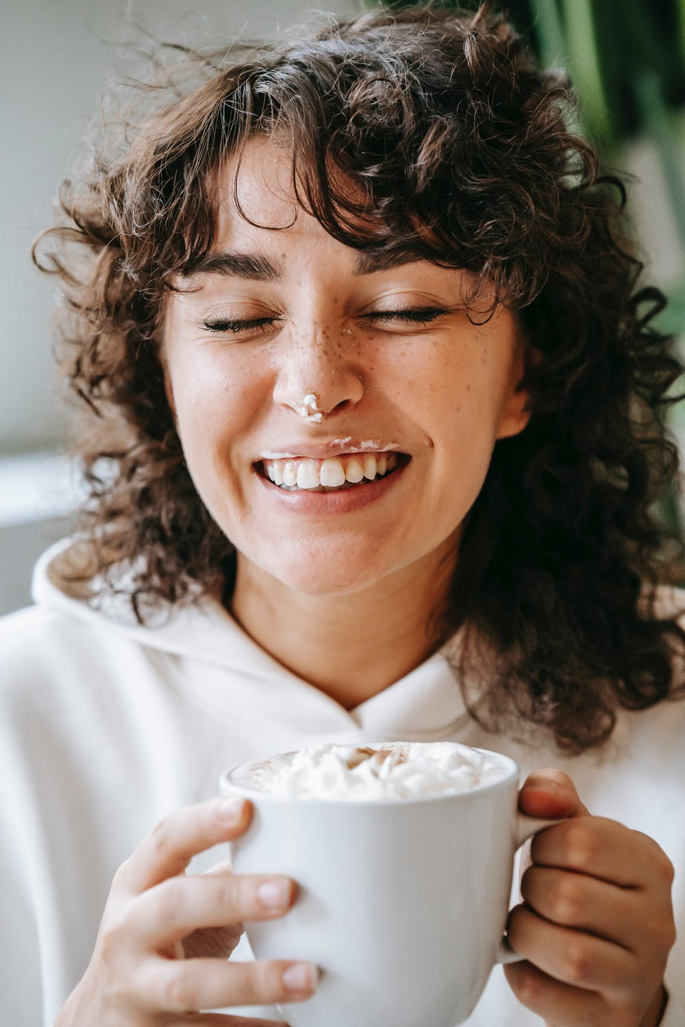 woman sipping hot chocolate with whipped cream on her nose