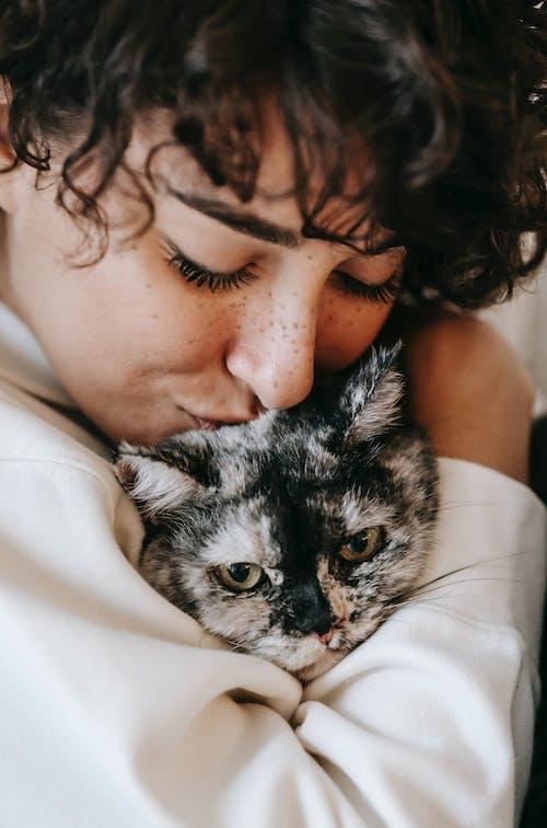 Mulher De Camisa Branca Com Um Gato Cinza E Branco No Peito