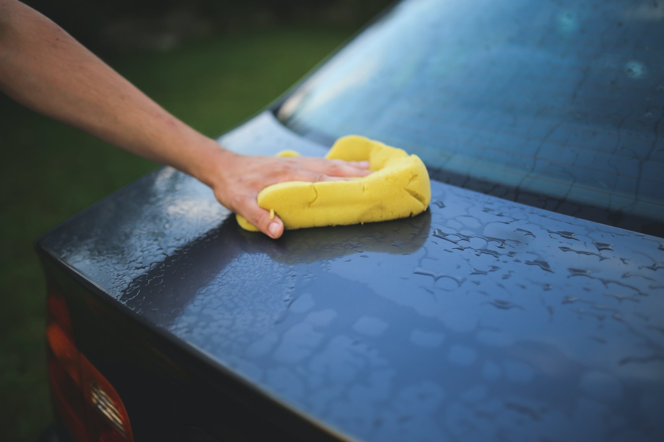 A person cleaning their car.