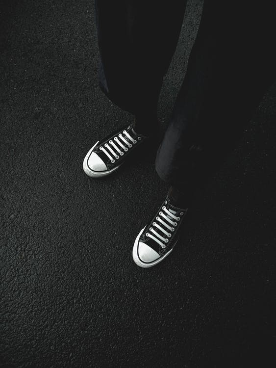 From above black and white of unrecognizable person wearing pants and trendy footwear while standing on asphalt in city on street