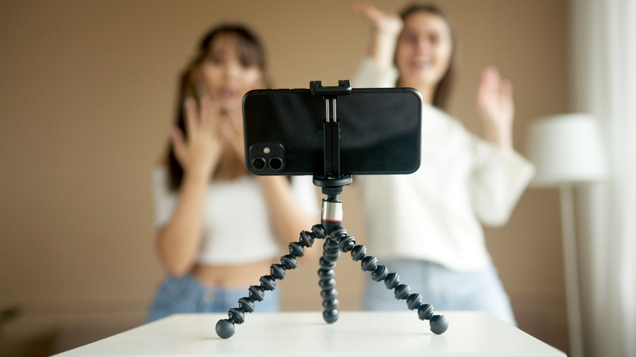Black Camera on Tripod in Front of Woman in White Shirt