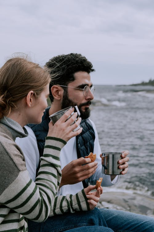Man and Woman Holding Drinking Glass Near Body of Water