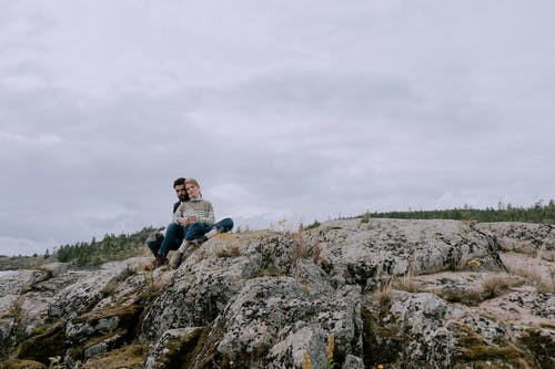 Man in Blue Shirt Sitting on Rock Formation