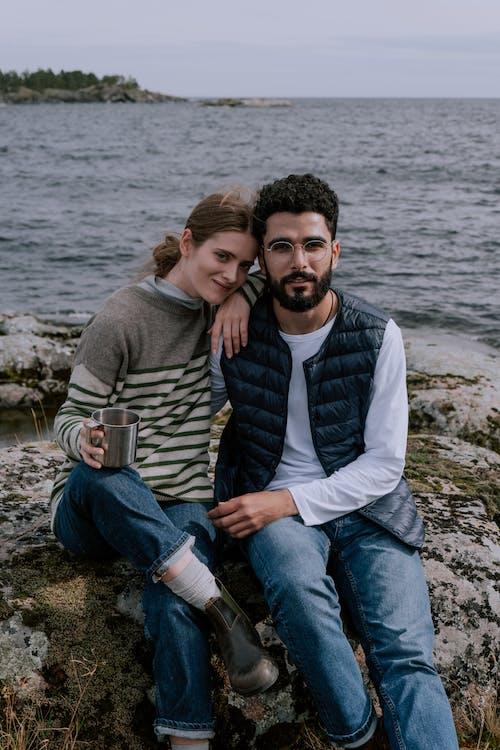 Man in Gray Sweater Sitting Beside Woman in Gray Sweater