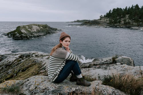 Woman in Gray and Black Striped Sweater and Blue Denim Jeans Sitting on Rock Near Body