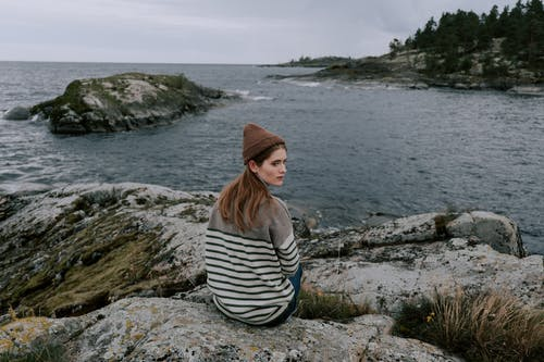 Woman in White and Black Striped Shirt and Brown Fedora Hat Sitting on Rock Near Body