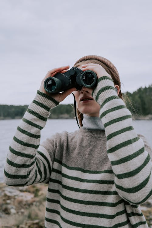 Person in Gray and White Striped Long Sleeve Shirt Using Binoculars