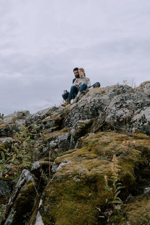 Man in Blue Jacket Sitting on Rock