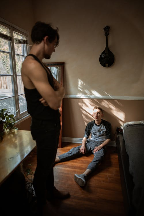 Man in Black Tank Top and Pants Looking at a Boy Sitting