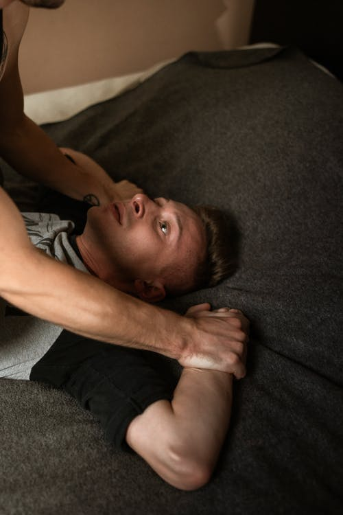 Boy in Gray Shirt Lying on Bed