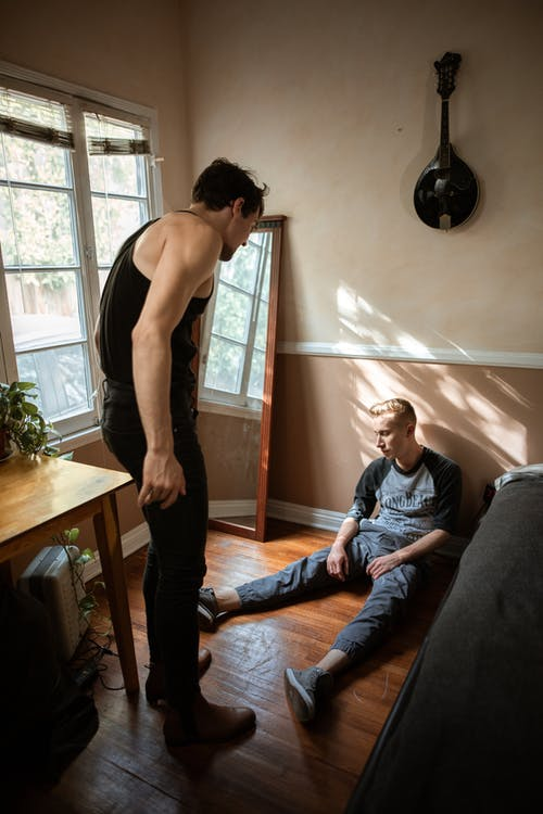 Man in Black Pants Talking to a Boy Sitting on the Floor