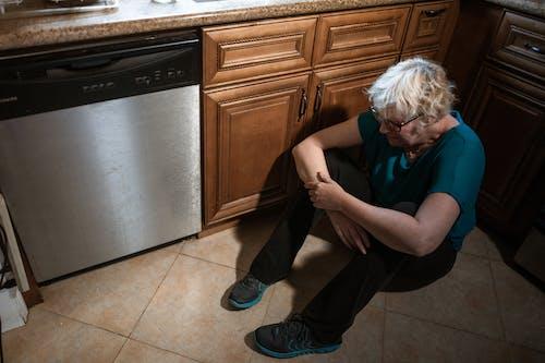 綠色的襯衫和黑色的褲子,坐在廚房櫃檯上的女人