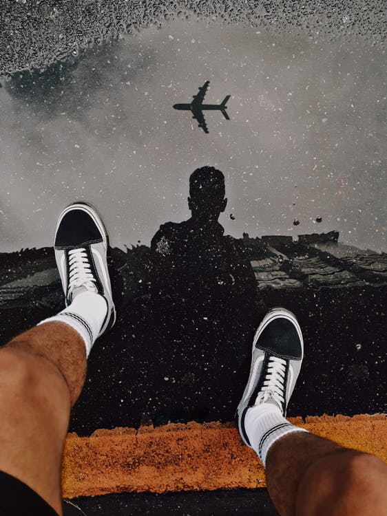 Person Wearing Black and White Adidas Sneakers