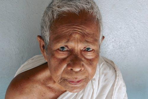 Serious Asian senior man near white wall
