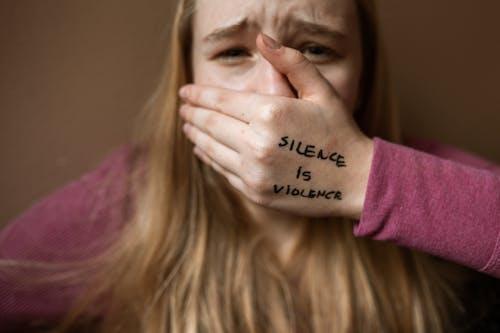 紫色的襯衫,遮住她的臉,用她的手的女人