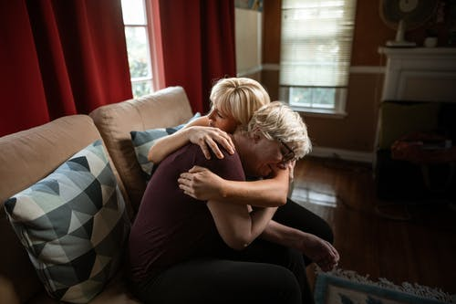 Woman Embracing Crying Elderly Woman While Sitting on Couch