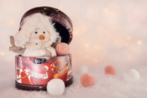 Small decorative snowman in hat and scarf placed in round box on white surface with artificial snowballs during Christmas holiday