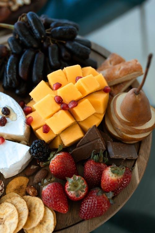 茶色の木製ボウルにスライスしたチーズとイチゴ
