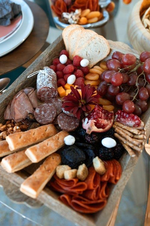 茶色の織りトレイにスライスされたパンとブドウ