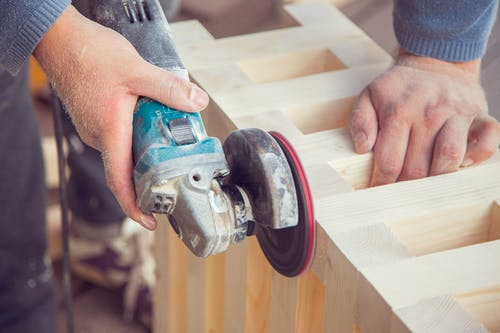 Crop unrecognizable male carpenter using angle grinder to polish wooden construction in light joinery