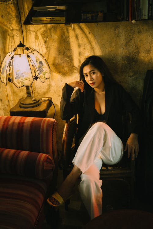 Stylish ethnic lady resting in armchair