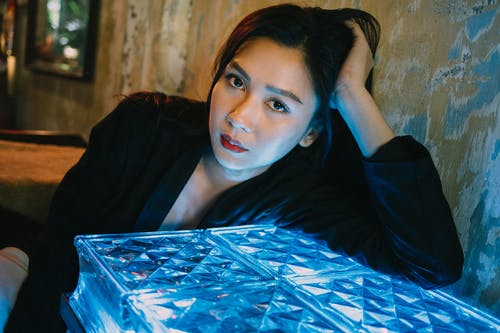 Serious Asian lady looking at camera while resting in cozy cafe while leaning on neon table with lamps