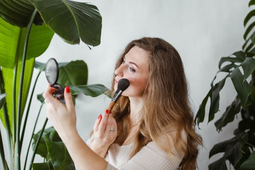 Photo of a Blonde Woman Applying Makeup on Her Cheeks