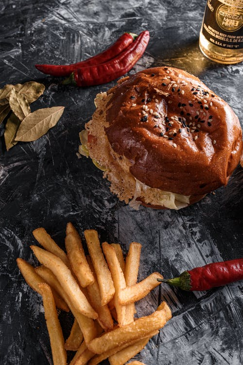 Composition of delicious burger and french fries on gray table