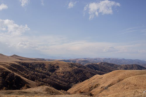 Picturesque scenery of vast hilly valley covered with dry vegetation against cloudless blue sky
