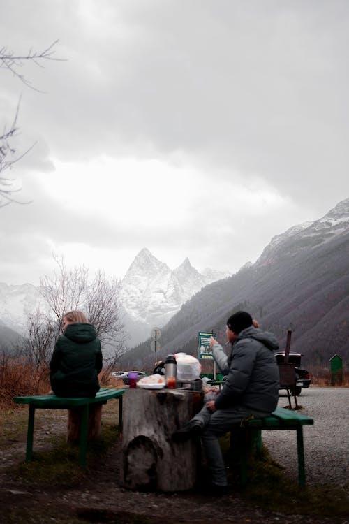 Unrecognizable travelers having lunch in mountainous terrain