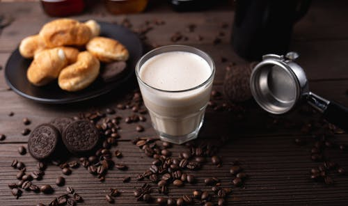 Glass of milk on table near pastries and coffee beans