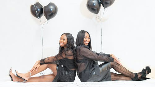 Side view of cheerful African American women in stylish black dresses sitting in studio against balloons and white wall
