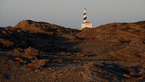 White and Brown Lighthouse on Brown Hill