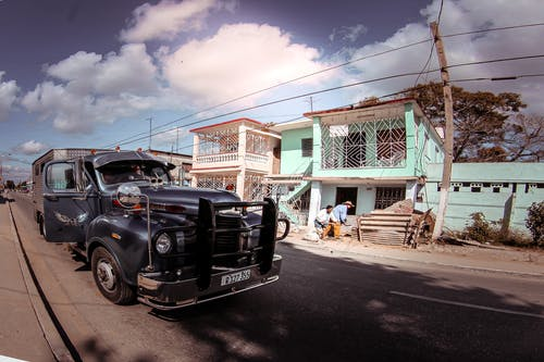 Aged pickup vehicle on rough roadway against building facade and unrecognizable ethnic partners under blue cloudy sky in town