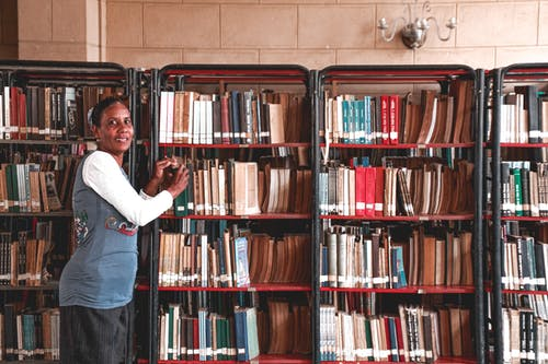 Side view of content mature Hindu female picking textbook from bookcase with assorted literature while looking at camera in library
