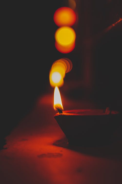 Small decorative diya candle placed on surface in darkness for Indian religious festival