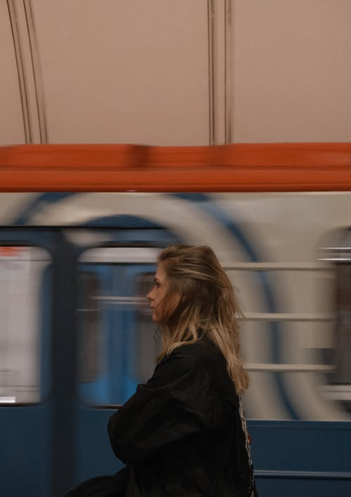 Woman standing in metro station near moving train