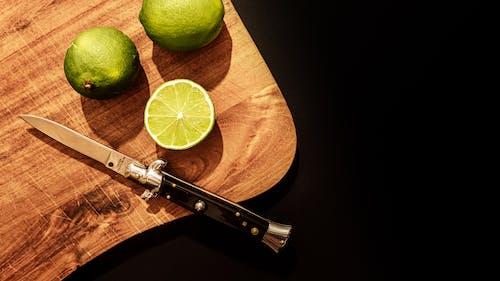 Sliced Lemon Beside Silver Knife on Brown Wooden Table