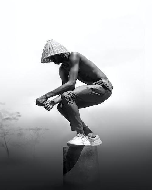 Uomo In Pantaloni Neri E Statua Del Cappello