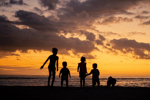 Silhouettes of children on beach at sunset