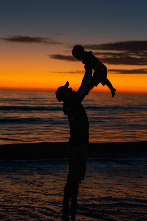 Silhouette of man carrying son on shore