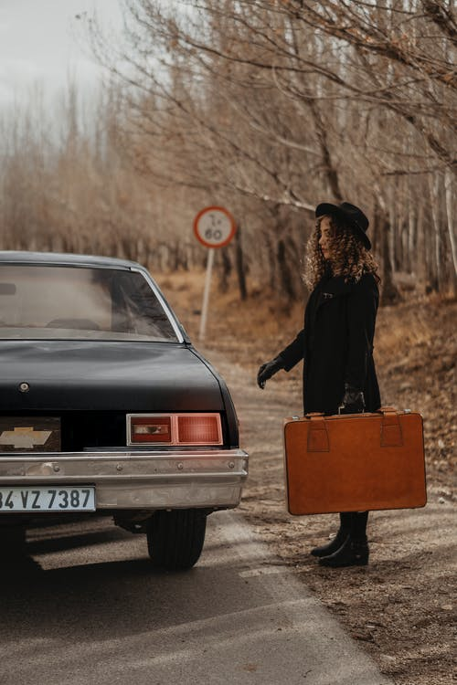 Side view of young stylish female catching old automobile on road with leafless trees in autumn