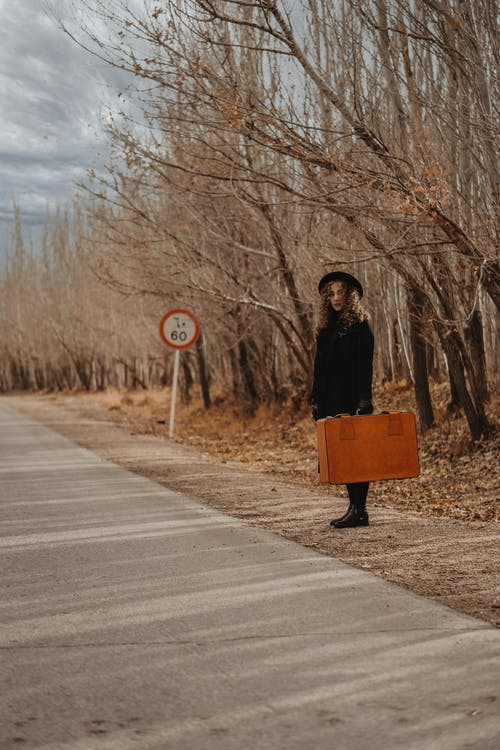 Full body of female in elegant outfit and hat with old suitcase near leafless trees in autumn