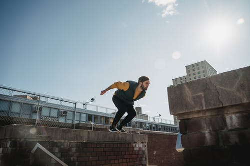 Full body of bearded male in activewear jumping on concrete structure while doing parkour exercises