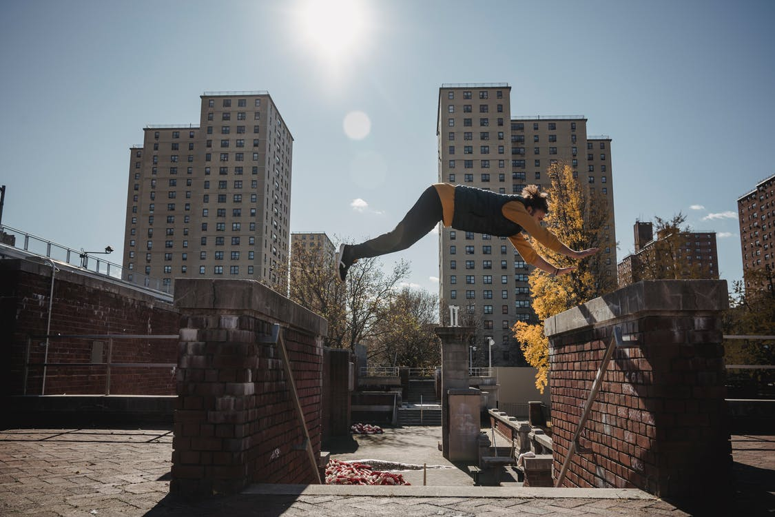 Side view of faceless male athlete performing trick in jump while training in sunny city