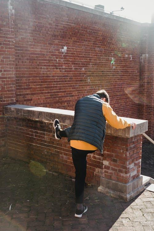 Anonymous man jumping over brick border