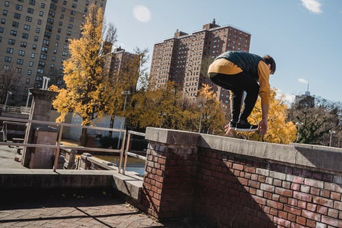 Unrecognizable male in activewear performing stunt while practicing parkour on street of city
