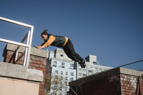 Full length of bearded man in activewear jumping high while performing parkour trick in city