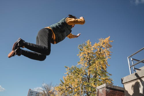 Strong faceless man jumping on roof